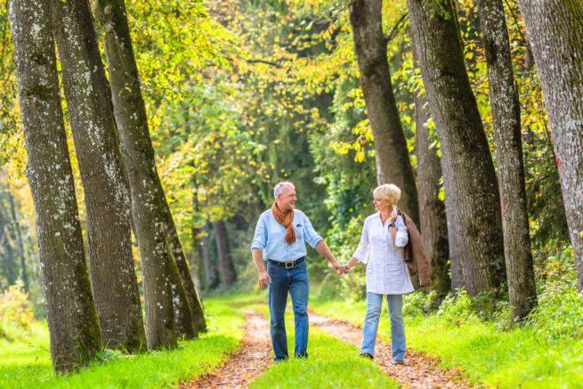 Senior couple having leisure walk in woods
